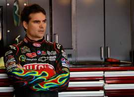Jeff Gordon, driver of the No. 24 DuPont Chevrolet, stands in the garage area - Photo Credit: Chris Trotman/Getty Images for NASCAR