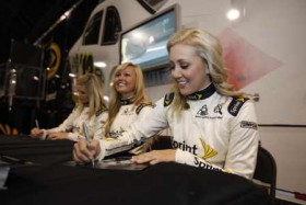 The 2012 Miss Sprint Cup lineup, with newcomer Kristen Beat, center, joining Kim Coon, left, and Jaclyn Roney, signs autographs during the NASCAR Preview presented by Sprint on Jan. 21, 2012, in Charlotte, N.C. - Photo Credit: Chris Graythen/Getty Images for NASCAR