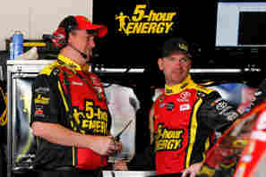 Clint Bowyer, driver of the #15 5-Hour Energy Toyota, speaks to Crew cheif Brian Pattie in the garage - Photo Credit: Tyler Barrick/Getty Images
